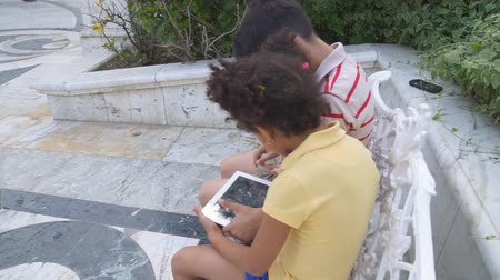 boy and girl sitting on a bench and using the tablet
