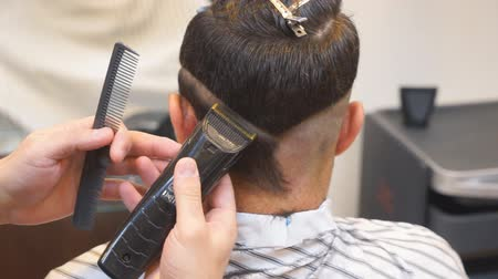 Close up of men haircut with clipper in the barbershop.Haircut men Barbershop. Men Hairdressers. Barber cuts the client machine for haircuts.
