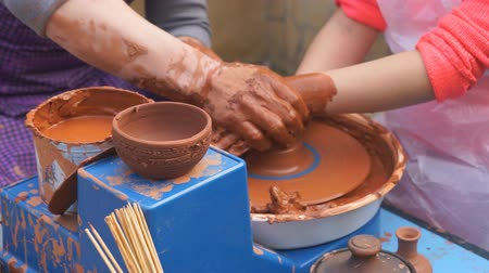 louça de barro : Hands of potter teaches the child how to make pots. Concept - transfer of experience,