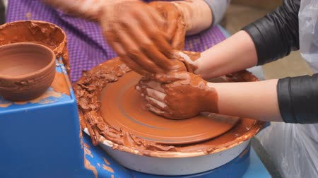 brocca : Hands of potter teaches the child how to make pots. Concept - transfer of experience,