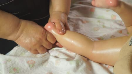 A woman makes a baby a foot massage