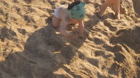A little boy is playing on the sand on the beach. A baby crawls and laughs studying all around. Dostupné videozáznamy