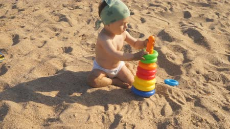 A little boy is playing on the sand on the beach. A baby crawls and laughs studying all around. Wideo