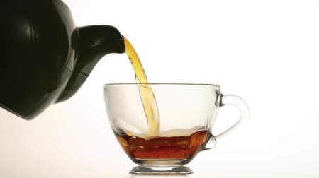 herbata : Pouring hot tea into glass cup isolated on white background