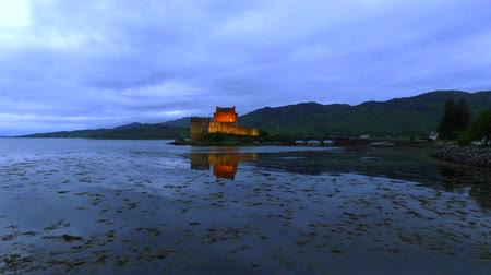 aeródromo : Illuminated Eilean Donan Castle over the lake at sunset in Scotland Stock Footage