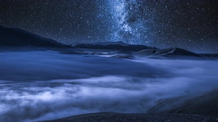 toscana : Milky way over flowing clouds in Castelluccio mountains at night, Italy, timelapse, 4K Vídeos