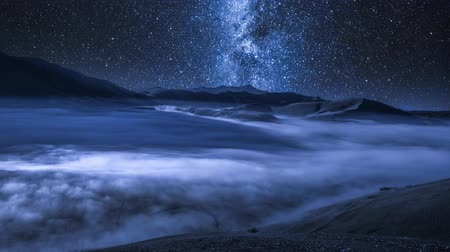 astro : Milky way over flowing clouds in Castelluccio mountains at night, Italy, Europe Stock Footage