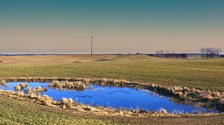 carvão gigante : Wind turbine and small blue pond in sunny day, aerial view Vídeos