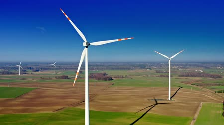 устойчивость : Wind turbines with blue sky on farm field, aerial view Стоковые видеозаписи