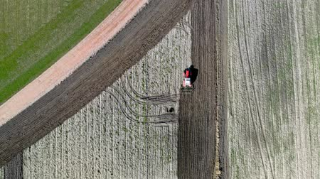 ploughing : Red tractor plowing field, aerial view in spring