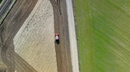 ploughing : Red tractor plowing field in Poland, aerial view in spring