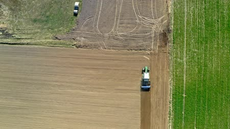 plowed land : Aerial view of green tractor plowing a spring field, Poland