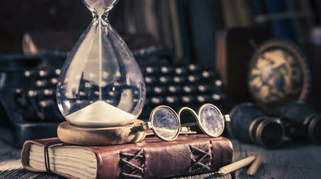 múlt : Moving sand in an hourglass, old diary and binocular, retro style