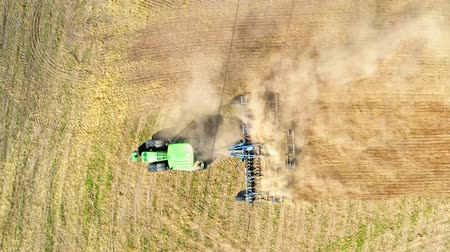 ploughing : Aerial view of green tractor plowing dry field