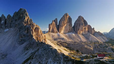 tre : Stunning mountain shelter above Tre Cime at sunset, aerial view