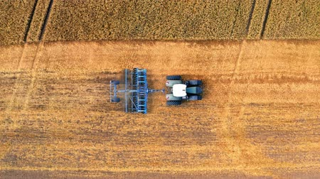 plowed land : Aerial view of blue tractor plowing field after harvest