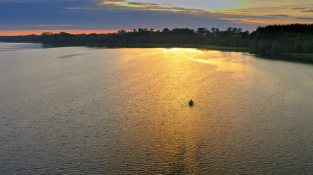 Aerial view of lonely boat on lake at sunset