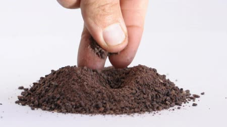 Closeup of mans fingers rubbing a pinch of raw cocoa powder