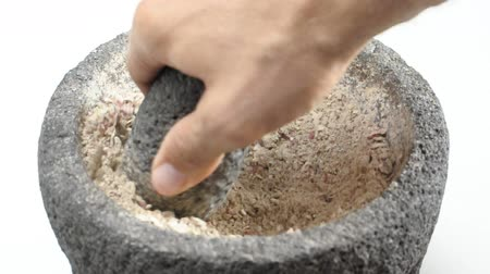 Grinding dried potato in mortar and pestle