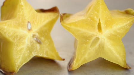 Hand places cut star fruit on table