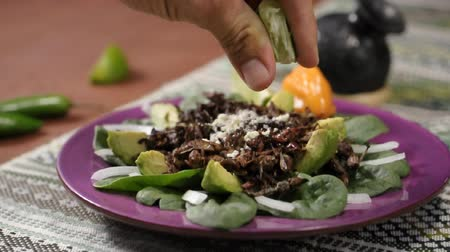 meyve suyu : Fingers of man squeezing a lime over a plate of roasted Mexican grasshoppers