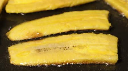 Closeup of slices of plantain bananas frying in pan with hot oil