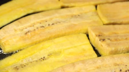 cozinhar : Several slices of plantain bananas frying in pan with hot oil