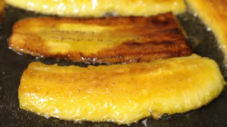 Closeup of sliced plantain bananas frying in pan with oil
