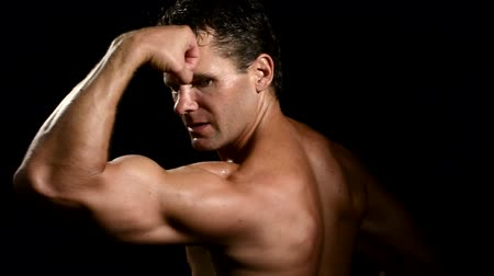 сильный : Muscular sweaty caucasian man performs biceps poses on black background