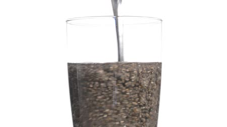 grubas : Closeup glass of water and soaked plump chia seeds stirred with spoon on white background