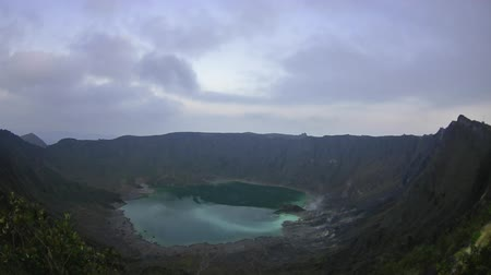 fumaroles : Dim light of morning and clouds over the crater and lake of El Chichonal volcano in Chiapas, Mexico Stock Footage