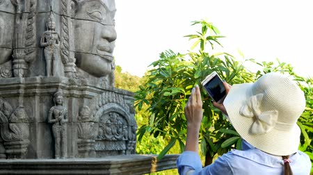 elfog : The girl photographs on the smartphone the ruins of an ancient city.