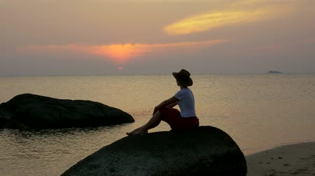 wistful : A girl at sunset sits on a rock looking out into the ocean.