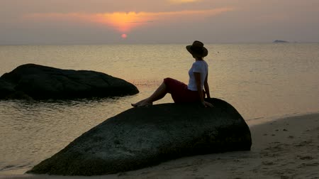 wistful : Nice girl in hat on the beach sits on a stone meets the sunset