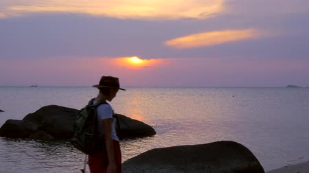 wistful : A girl with a backpack walks along the beach in sunset rays Stock Footage