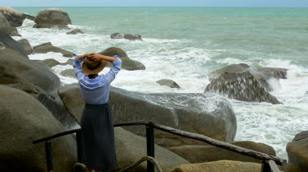 horizont : A girl raises her arms up meeting an ocean breeze