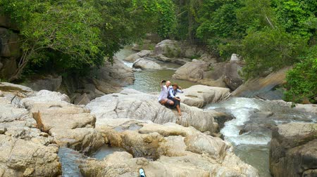 photograph : A pair of young people doing selfie on a background of mountain river