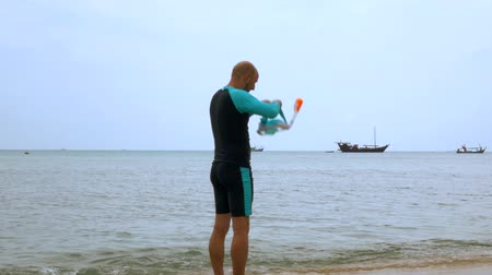 nadador : A man walks into the sea dresses a full face mask.