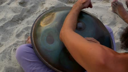 perkusja : Close up hands playing hang drum music instrument on the beach