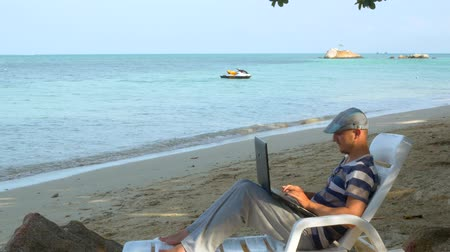 chaise longue : Man typing on a laptop enjoying the summer sunshine while on vacation on the beach Stock Footage