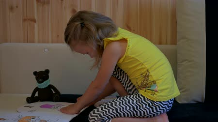 young animal : Little girl on the sofa draws. Stock Footage