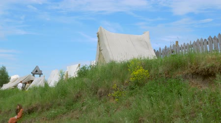 sivil : girl sits on the slope behind the tent, historical reconstruction Stok Video