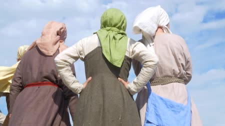 from behind : Group Girls in vintage dresses and scarves are talking. In the background of the sky and clouds Stock Footage