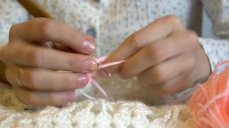 hímzés : A woman knits a scarf with white and pink wool. Stock mozgókép