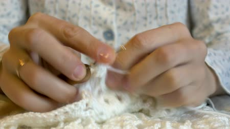 meada : woman crochets beautiful patterns with white woolen threads