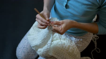 meada : the woman is sitting, crocheting beautiful patterns with white woolen threads Stock Footage