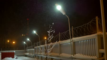 farpa : Forbidden zone at night in a blizzard. Behind the fence with barbed wire. Enclosed object Stock Footage