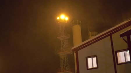 прожектор : in a blizzard at night at the factory, illuminated by a searchlight, the window lights up Стоковые видеозаписи