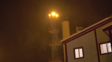 прожектор : the blizzard plant is illuminated by a searchlight, the lights are on in the window