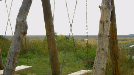 меланхолия : Wooden swing with a beautiful view of nature in the village.